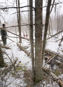 A Michigan Department of Natural Resources conservation officer investigates snares that Pickford resident Kurt Johnston Duncan was charged with using to illegally capture animals. Courtesy photo