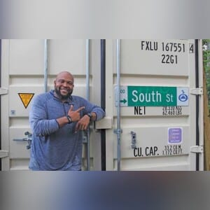 Raymond Warthen, founder of the South Street Farm in the Parramore neighborhood, posed in front of one of the shipping containers that is used for storage at the farm on July 2. S.T. CARDINAL